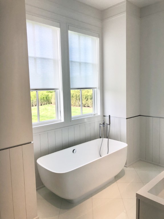 solar shades in a balmoral fabric and encased in a wrapped fascia bathroom